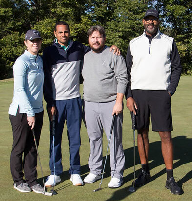 group smiling at a golf tournament