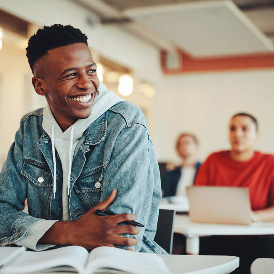 young adults in a classroom smiling